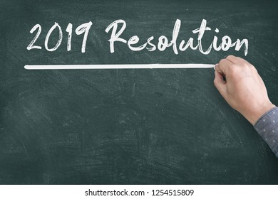 Close up of human hand writing 2019 New Year Resolution Check List on Blackboard
