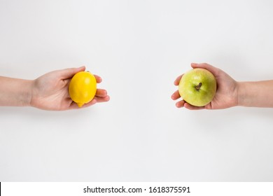 Close up of human hands exchanging different products isolated on white. Food sharing between people. Give a friend healthy fruits as present. Person swap, GMO versus BIO organic nutrition concept.