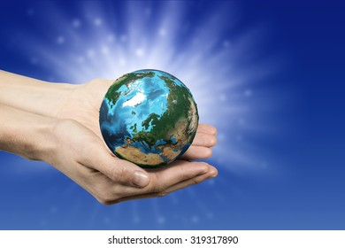 Close up of human hands holding Earth planet. Elements of this image are furnished by NASA