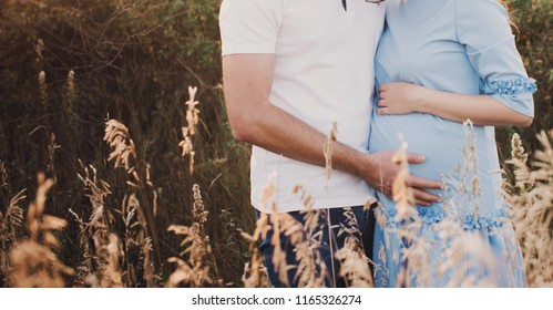 Close up of human hands holding pregnant belly, closeup happy family awaiting baby, standing on green grass, body part, young family and new life concept