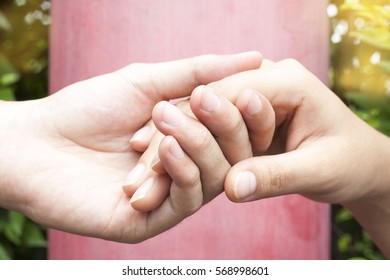close up human hands holding together on red background , Help and support concept