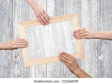 Close up of human hands holding wooden frame