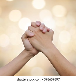 close up human handshake on blur gold color background with bokeh light for confident,success and victory concept.