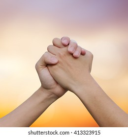 close up human handshake on blur gold sunset colorful background for world labour day concept.