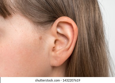 Close up of human head with female ear - listening or deafness concept