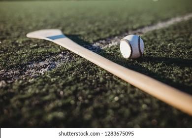 Close up of hurl and Sliotar on gaa pitch