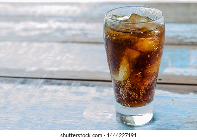 close up ice with cola in glass on wood table.