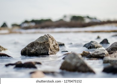 Close up of ice and rocks on the beach in Kennebunk Maine. Below freezing temperatures lets ice form on the sandy beach in new england