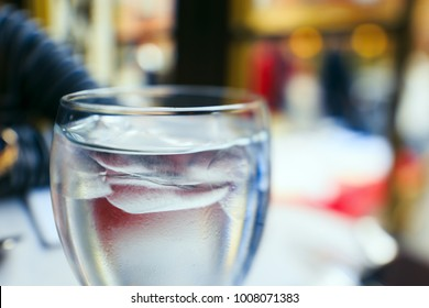 A close up of a ice water glass served in a restaurant with shallow depth of field.