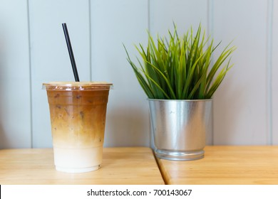 close up of iced latte coffee in transparent plastic glass and straw with mock up plant on the wooden table. coffee and cafe decoration concept.
