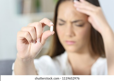 Close up of an ill woman hand showing a painkiller pill