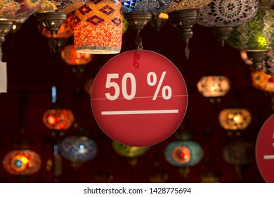 Close up image of a 50% discount label with white sans serif text on red flat cartoon hanging from a ceiling full of ornamental glass lamps in an interior.