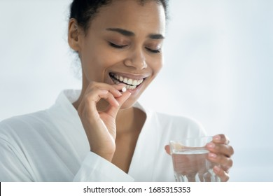 Close up image african 35s female holding glass of still water and round white pill. Taking dose of daily multivitamins for women, caring about skin nail and hair vitamins, healthy lifestyle concept