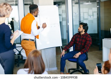 close up image of african office manager showing chart on flipchart to his Hindu boss and co-workes
