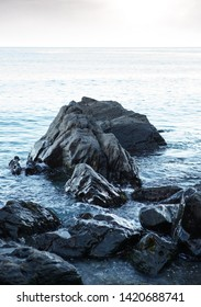 close up image in almunecar spain of large rocks going into the sea on a calm and gentle day
