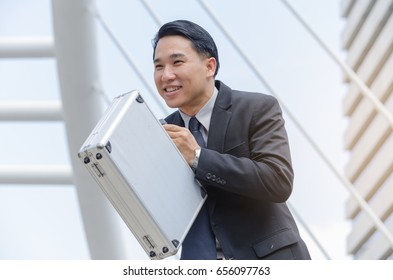 Close up image of Asian business man standing,holding briefcase and smile,happy life concept.