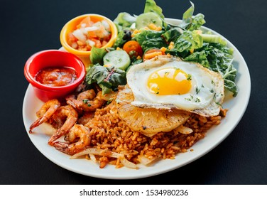 Close up image of Asian pineapple fried rice with fried egg,shrimp,and vegetables salad on a white plate