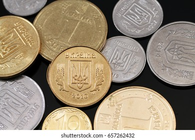 A close up image of assorted Ukrainian coins on a black background
