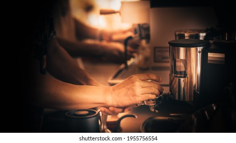 close up image of barista grinding fresh roasted specialty coffee in to professional machine. process of brew coffee making in a coffee house