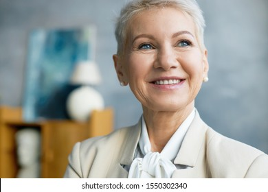Close up image of beautiful mature Caucasian female CEO with bonde pixie hairstyle smiling broadly and looking up thinking about future business plan and goals, her eyes expressing confidence