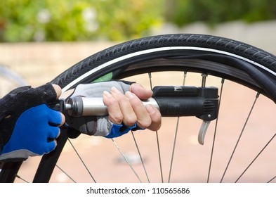 Close up image of a bicycle repair, with two hands in biker gloves, with valve, tube, alloys and a bike in the blurred background.