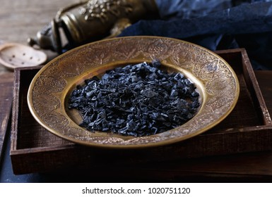 Close up image of Black sea salt in a brass plate on a rustic wooden box on wooden background. Selective focus