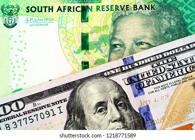 A close up image of a blue American one hundred dollar bill with a ten South African rand bank note