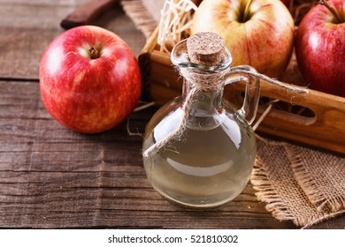 Close up image of a bottle of unfiltered apple cider vinegar and apples in a wooden box over rustic background close up