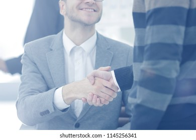 Close up image of business partners handshake over office desk during meeting
