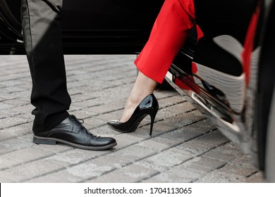 Close up image of a business woman getting out of her car with high heels shoes.