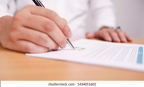 Close up image of businessman signing contract or student having exam test, selective focus