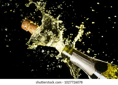 Close up image of champagne cork flying out of champagne bottle. Celebration theme with explosion of splashing champagne sparkling wine on black background.