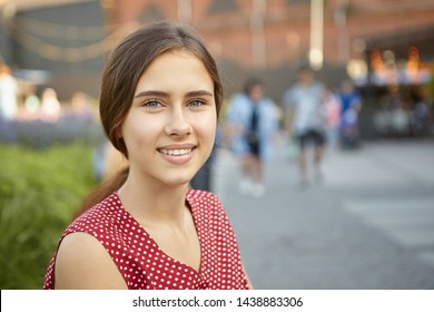 Close up image of charming gorgeous young woman with perfect tanned skin, straight teeth and hair gathered in ponytail looking at camera with positive beautiful smile, posing outdoors in park