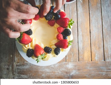 Close up image of a chef decorating a carrot cake with icing and creating a naked cake.