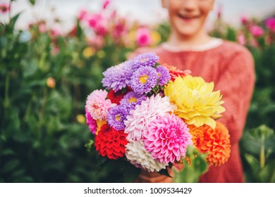 Close up image of colorful dahlia and chrysanthemum flowers bouquet holding by a child