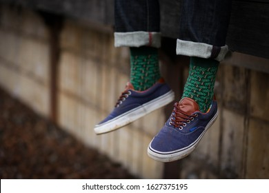 Close up image of dangling feet in blue shoes with vibrant green socks covered in palm trees