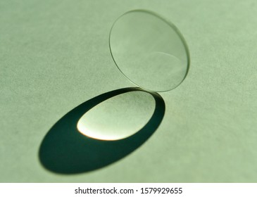 Close up image of daylight shine through clear circular convex lens with refection and refraction of light and cast artistic oval shape of shadow on white textured paper