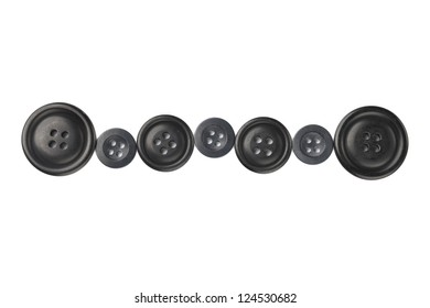 Close up image of different sizes of black cloth buttons against white background