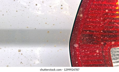 Close up image of a dirty silver car, red backlight