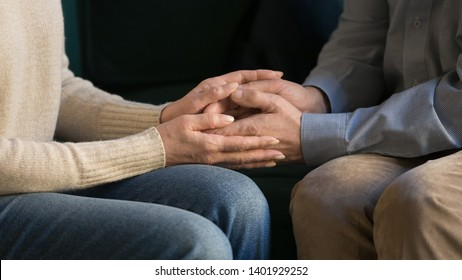 Close up image of elderly couple in love sitting on couch holds hands, loving wife supporting encouraging beloved husband show empathy, understanding in relations, moral and psychological help concept