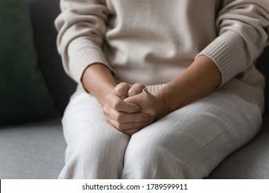 Close up image elderly woman feels nervous anxious or lonely put clenched hands on laps sitting on couch indoors. Older patient of nursing home, senile diseases and geriatric, declining years concept