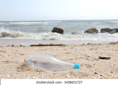 close up image of empty plastic water bottle on dirty beach filled with plastic pollution, garbage and waste on dirty sandy beach
