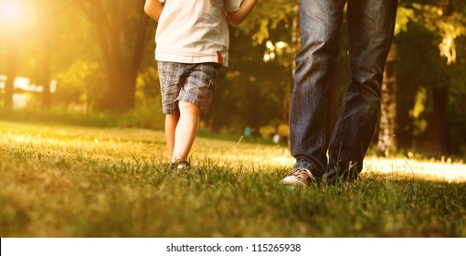 Close up image of father and son legs walk across the lawn in the park
