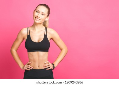 3b2e598271 Close up image of female in sports clothing relaxing after workout on pink  background. Muscular