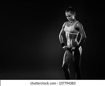 Close up image of  female in sports clothing relaxing after workout on dark background. Muscular female body with sweat. Image with copyspace for text