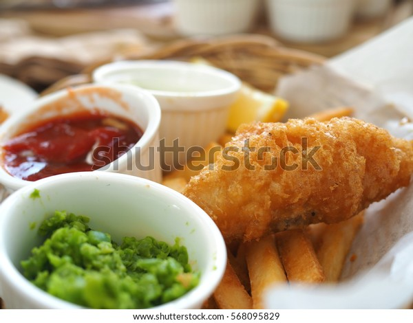 Close up image of fish and chips in the basket with sauces