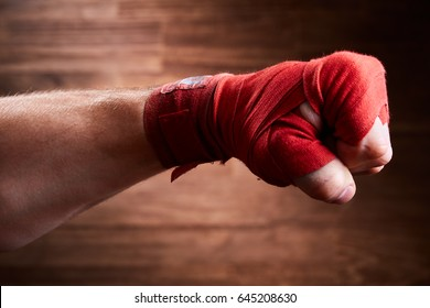 Close up image of fist of a boxer with red bandage against brown background.