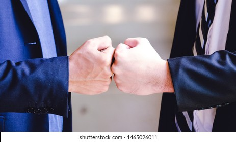 A close up image of a fist bump in vintage tone. Hands of young people show strength teamwork in the nature, team concept.