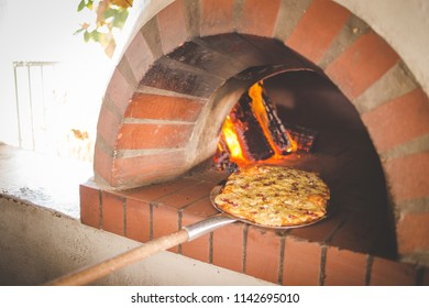 Close up image of a freshly baked gourmet wood fired pizza as it gets taken out of the pizza oven