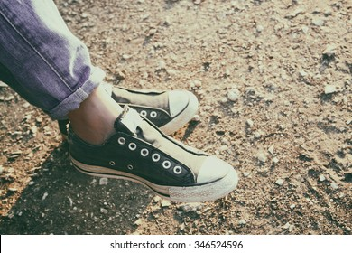close up image of girl in sneakers sitting on the bench. filtered image